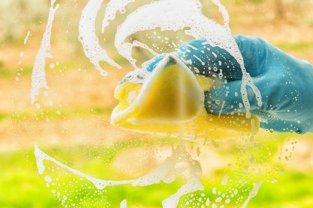 Ręka w gumowej rękawicy myje okno Premium Zdjęcia