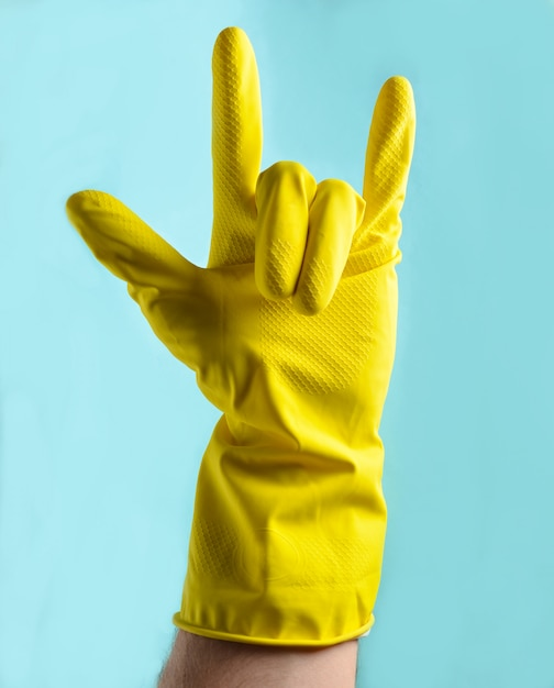 Ręka W żółtych Gumowych Rękawiczkach Pokazuje Skalny Róg, Dwa Palce W Górę Premium Zdjęcia