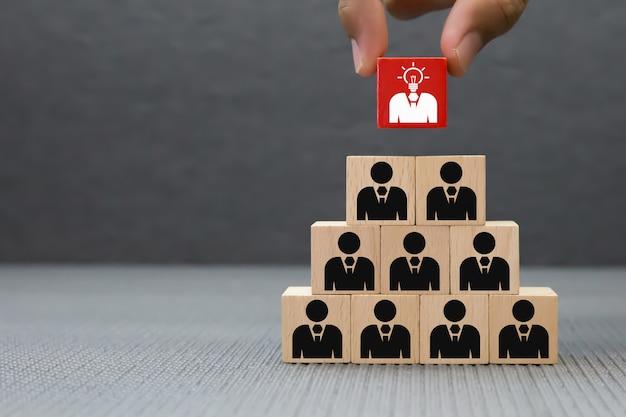 Ręka Wybiera Biznesmen Ikonę Na Drewnianym Bloku. Premium Zdjęcia