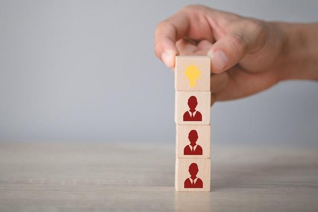 Ręka Wybiera Drewnianego Sześcian Z Ikony żarówką I Ludzkim Symbolem. Premium Zdjęcia