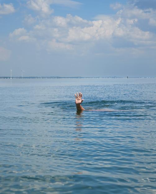 Ręka wystaje z wody pośrodku oceanu Premium Zdjęcia
