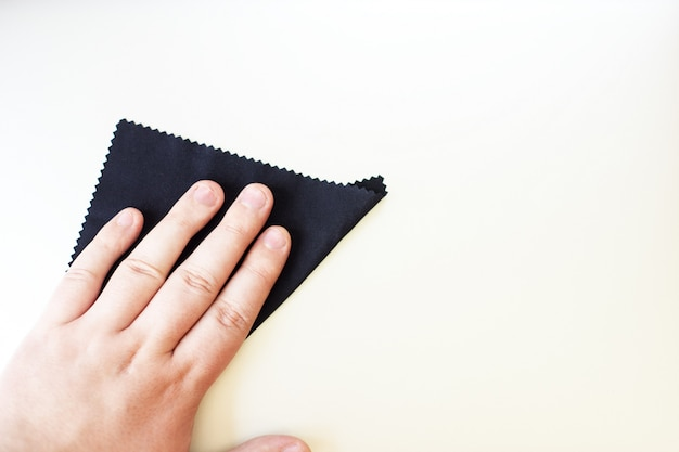 Ręka z czarnym rag czyszczenia na srebrnym tle Premium Zdjęcia