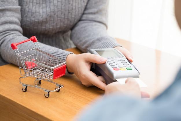 Ręka z machnięciem karty kredytowej przez terminal do zapłaty Premium Zdjęcia