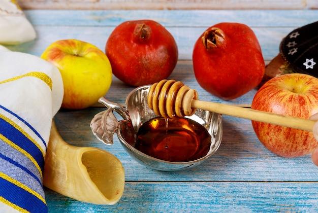Ręka Z Miodem Bierze Kawałek Jabłka I Granatu święto Rosz Ha-szana Premium Zdjęcia