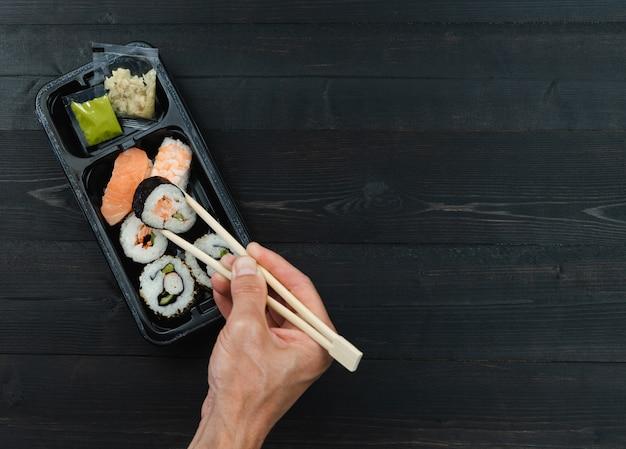 Ręka Z Pałeczkami I Tacą Sushi. Koncepcja Na Wynos. Premium Zdjęcia