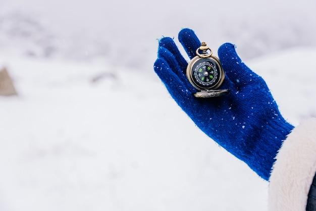 Ręka Z Wełnianymi Rękawiczkami, Trzymając Kompas W śniegu Premium Zdjęcia