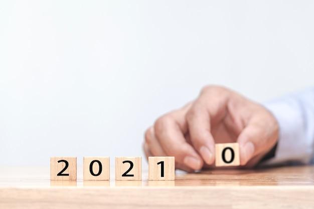Ręka Zmienia Drewnianą Kostkę Zmienia Się Symbolicznie Od 2020 Do 2021 Roku Premium Zdjęcia
