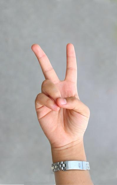 Ręka znak v koncepcja pokoju, walki, gestu ciała i słodkie Premium Zdjęcia