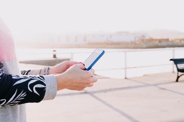 Ręki Kobieta Trzyma Telefonu Komórkowego Zakończenie Up Na Słonecznym Dniu Premium Zdjęcia