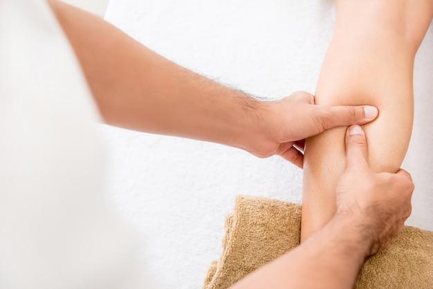 Ręki męski terapeuta daje masażowi kobiety noga Premium Zdjęcia