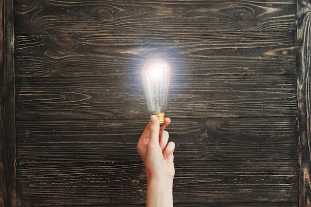 Ręki mienia żarówka na drewnianej desce Premium Zdjęcia