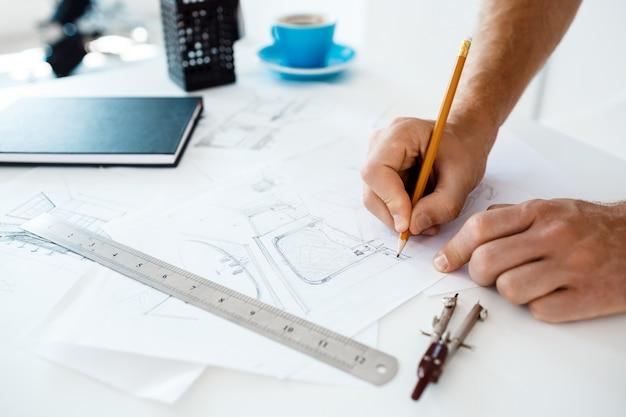 Ręki Młody Biznesmena Mienia Ołówek I Rysunek Kreślą Przy Stołem. Białe Nowoczesne Wnętrze Biura Darmowe Zdjęcia