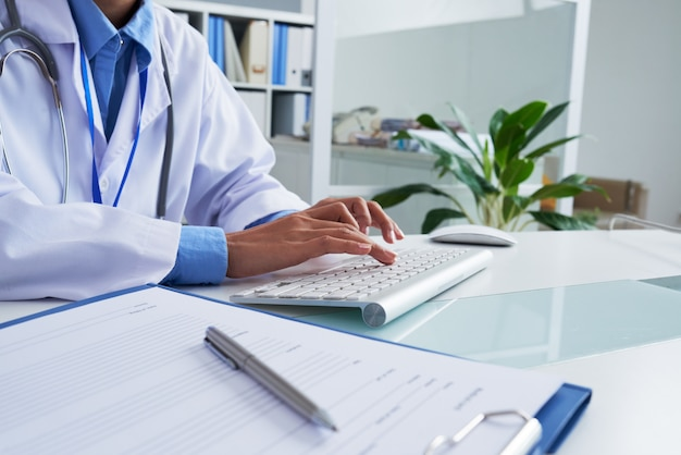 Ręki nierozpoznawalnej kobiety doktorski pisać na maszynie na klawiaturze w biurze Darmowe Zdjęcia