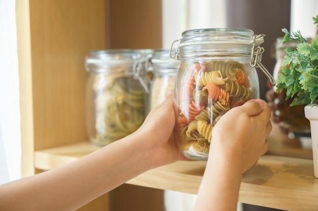 Ręki Podnosi Makaron W Szklanym Słoju Dla Przygotowywać Jedzenie Premium Zdjęcia