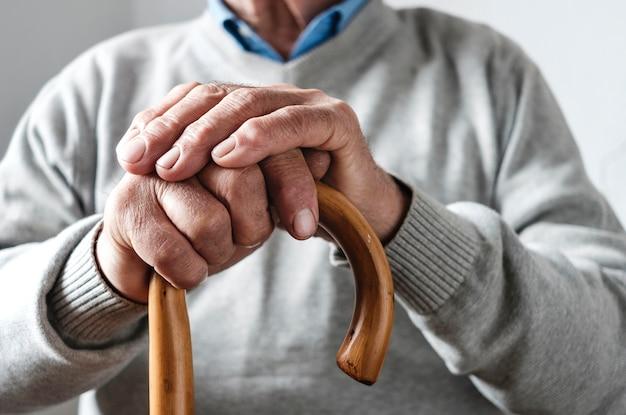 Ręki starszy mężczyzna odpoczywa na chodzącej trzcinie Premium Zdjęcia