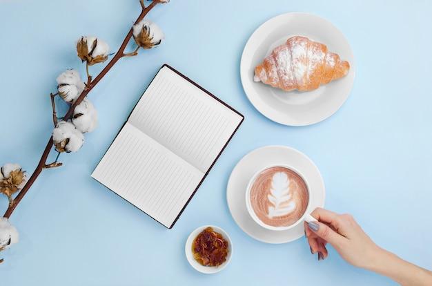 Ręki Trzyma Kawę I Notatnika Z Rogalikiem I Bawełny Gałąź Premium Zdjęcia
