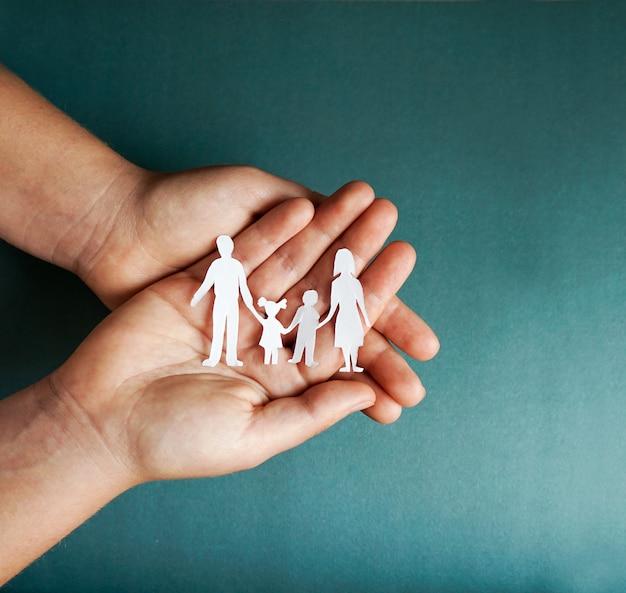 Ręki Trzyma Papierową Rodzinną Wycinankę, Ogólnospołeczny Dystansowy Pojęcie, Covid19 Na Błękitnym Koloru Tle, Rodzinna Ochrona Premium Zdjęcia