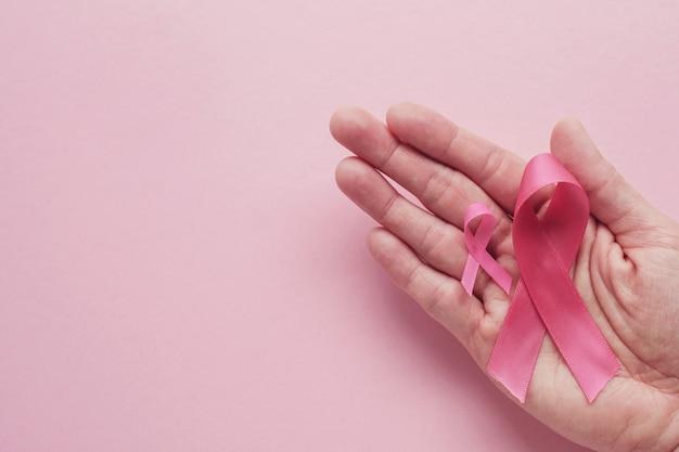 Ręki Trzyma Różowe Faborki Na Różowym Tle Premium Zdjęcia