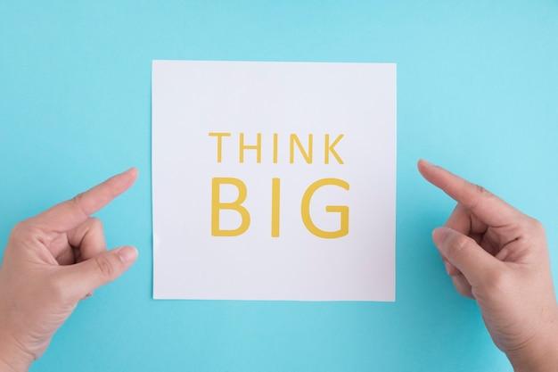Ręki wskazuje palec dalej myśleć dużego tekst nad białym papierem przeciw błękitnemu tłu Darmowe Zdjęcia