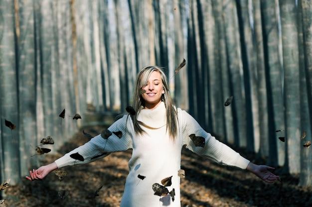 Relaxed Kobieta Bawi Się Z Liśćmi W Parku Darmowe Zdjęcia