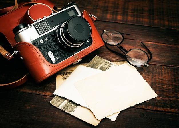 Retro Aparat I Kilka Starych Zdjęć Na Drewnianej Powierzchni Stołu Premium Zdjęcia