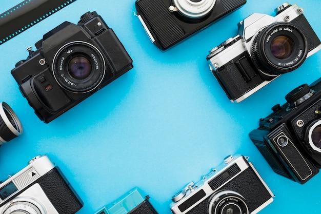 Retro aparaty fotograficzne w pobliżu kawałka filmu Darmowe Zdjęcia