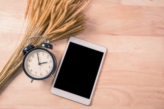 Retro budzik i inteligentny telefon cyfrowy tablet na drewno Premium Zdjęcia