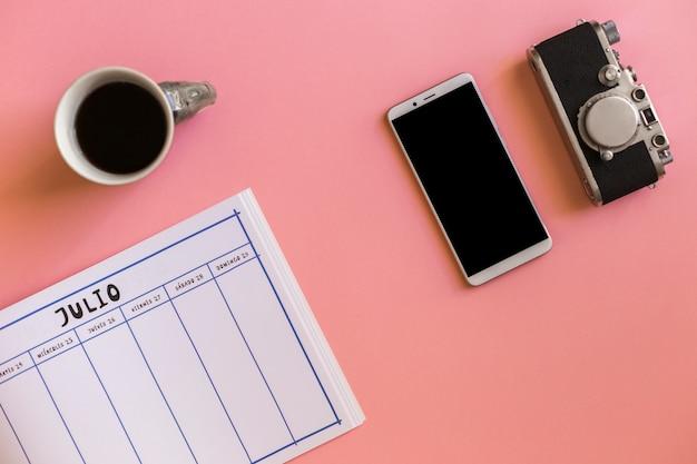 Retro kamera blisko smartphone, filiżanka napój i kalendarz Darmowe Zdjęcia