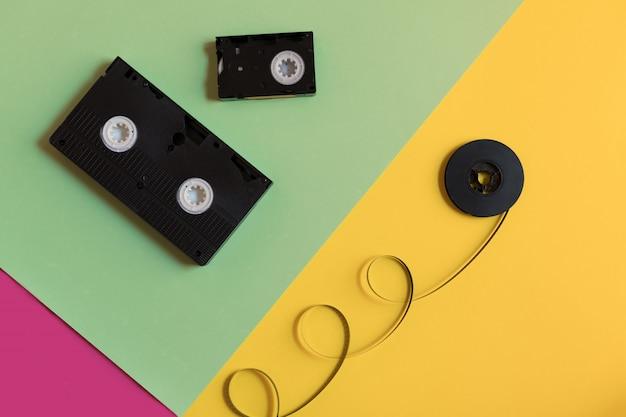 Retro Kaseta Wideo I Film Na Trzykolorowym Tle Pastelowego Papieru. Premium Zdjęcia