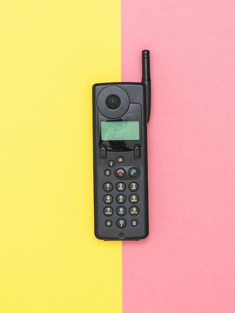 Retro Telefon Komórkowy Z Anteną Na żółto-różowej Powierzchni Premium Zdjęcia