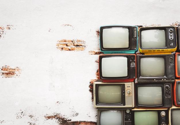 Retro Telewizory Wypiętrzają Na Podłoga W Starym Pokoju Z Biel ścianą Premium Zdjęcia