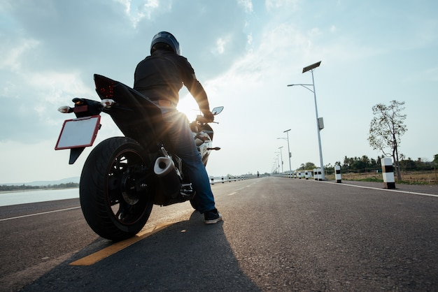 Rider motocykl na drodze. dobrze się bawiąc jeżdżąc pustą drogą Darmowe Zdjęcia
