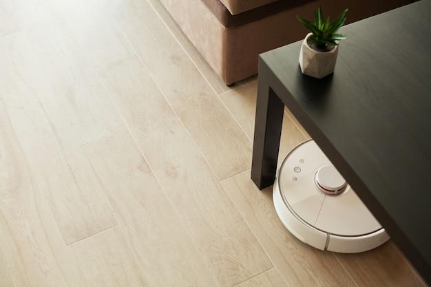 Robot Odkurzający Działa Na Drewnianej Podłodze W Salonie. Premium Zdjęcia