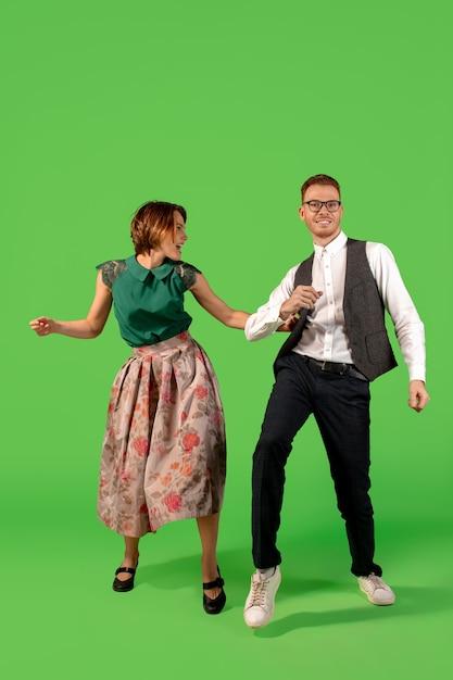 Rock N Roll. Old School Fashioned Młoda Kobieta Taniec Na Białym Tle Na Tle Zielonym Studio. Młody Elegancki Mężczyzna I Kobieta. Darmowe Zdjęcia