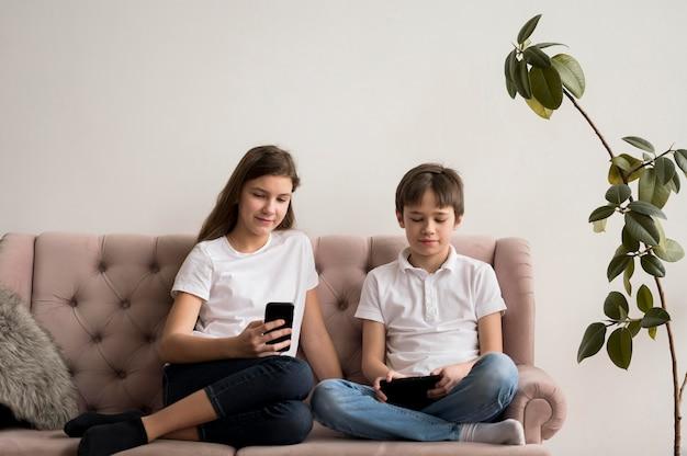 Rodzeństwo Korzystające Z Telefonu Komórkowego I Stołu Darmowe Zdjęcia