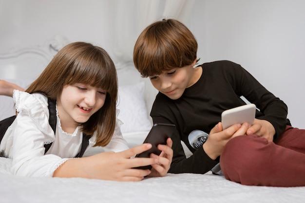 Rodzeństwo W Sypialni Z Telefonem Darmowe Zdjęcia
