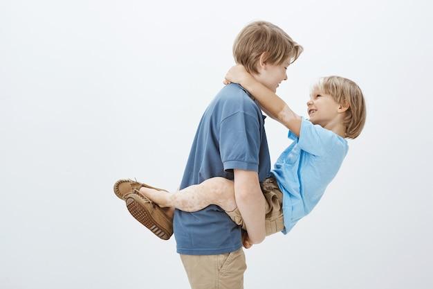 Rodzeństwo Zawsze Sobie Pomaga. Portret Beztroski Szczęśliwy Chłopiec Trzyma Brata W Ramionach I Uśmiecha Się Do Niego, Stojąc W Profilu Darmowe Zdjęcia