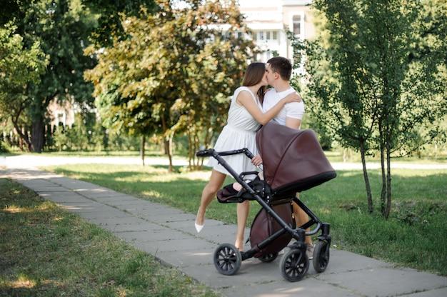 Rodzice Całują Się Obok Córki W Wózku Dziecięcym Premium Zdjęcia