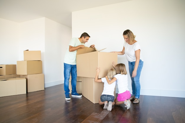 Rodzice I Dwie Córki Bawią Się Podczas Otwierania Pudeł I Rozpakowywania Rzeczy W Swoim Nowym Pustym Mieszkaniu Darmowe Zdjęcia