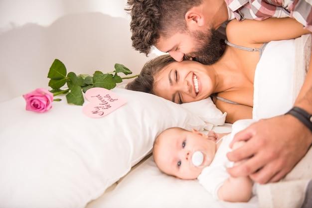 Rodzice z dzieckiem w łóżku w domu. Premium Zdjęcia