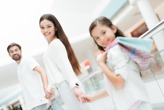 Rodzina, ojciec, matka i córka z torba na zakupy. Premium Zdjęcia