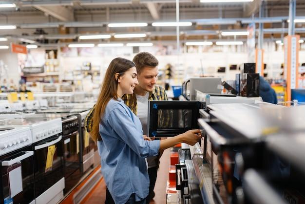 Rodzina Para Wybiera Kuchenkę Mikrofalową W Sklepie Elektronicznym. Mężczyzna I Kobieta Kupują Domowe Urządzenia Elektryczne Na Rynku Premium Zdjęcia