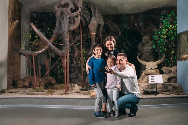 Rodzina Robi Sobie Selfie Przed Szkieletem Mamuta W Muzeum Paleontologii. Premium Zdjęcia