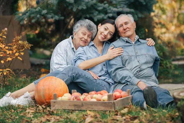 Rodzina Siedzi W Ogrodzie Z Jabłkami I Dyni Darmowe Zdjęcia