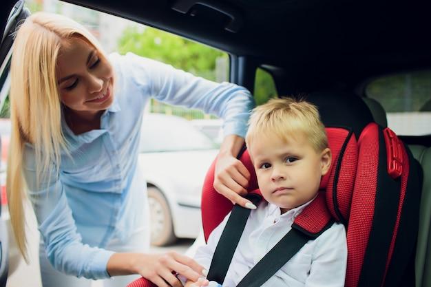 Rodzina, Transport, Wycieczka Samochodowa I Ludzie Pojęć, - Szczęśliwy Kobiety Uczepienia Dziecko Z Zbawczym Pasem Bezpieczeństwa W Samochodzie Premium Zdjęcia