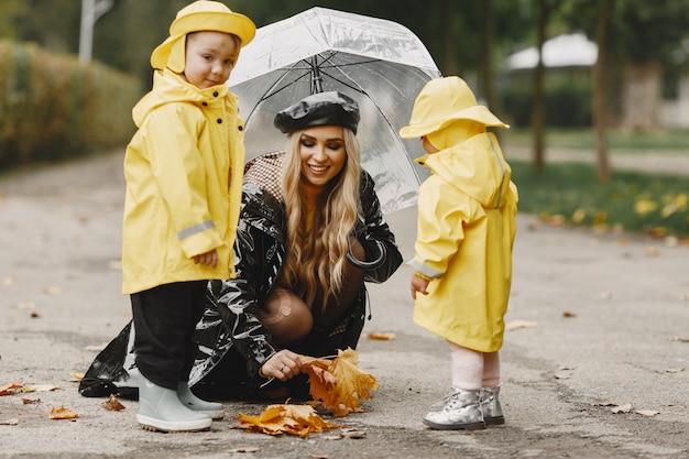 Rodzina W Deszczowym Parku. Dzieci W żółtych Płaszczach Przeciwdeszczowych I Kobieta W Czarnym Płaszczu. Darmowe Zdjęcia