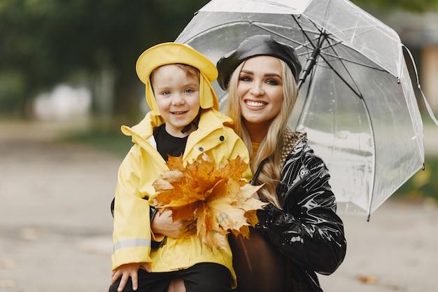 Rodzina W Deszczowym Parku. Dzieciak W żółtym Płaszczu Przeciwdeszczowym I Kobieta W Czarnym Płaszczu. Darmowe Zdjęcia