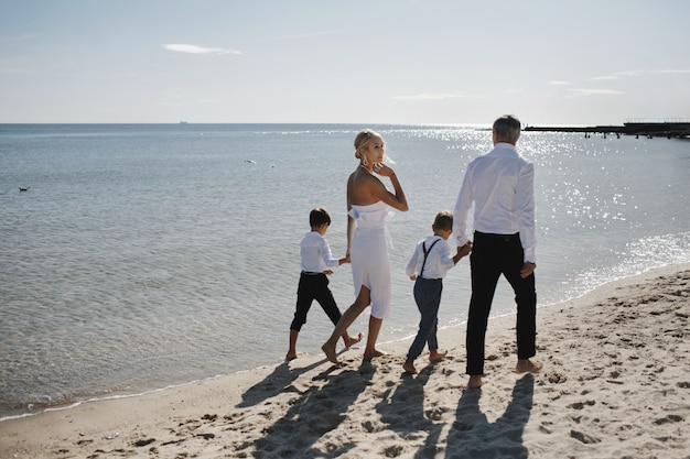 Rodzina W Luksusowych Ubraniach Chodzi Boso Po Piaszczystej Plaży W Ciepły, Słoneczny Dzień Darmowe Zdjęcia