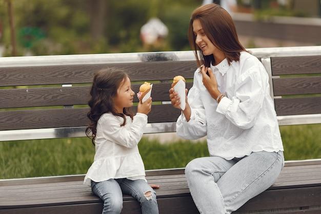 Rodzina W Mieście. Mała Dziewczynka Je Lody. Matka Z Córką Siedzi Na ławce. Darmowe Zdjęcia