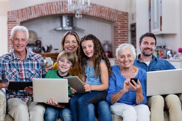 Rodzina wielopokoleniowa korzystająca z laptopa, tabletu i telefonu Premium Zdjęcia